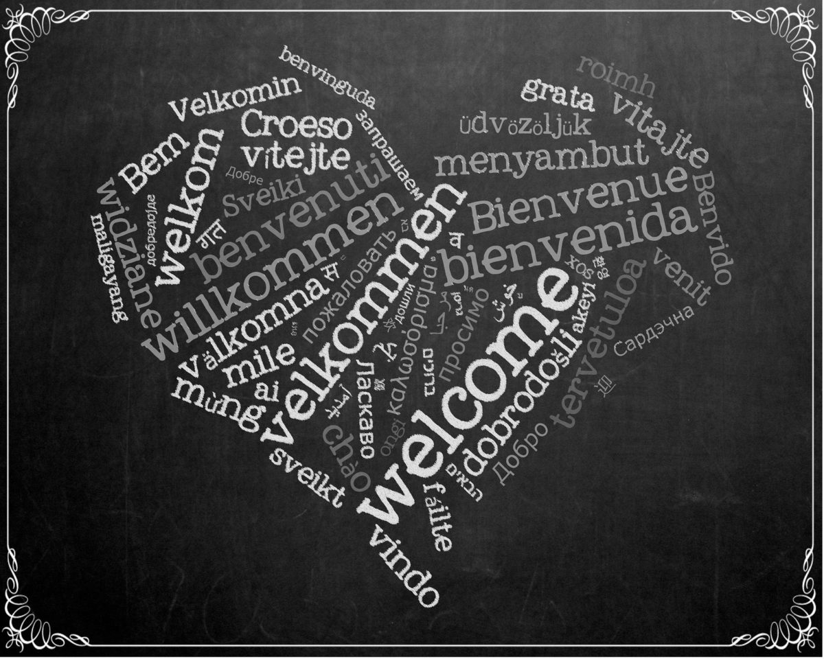Herz auf schiefertafel mit willkommen in vielen unterschiedlichen Sprachen